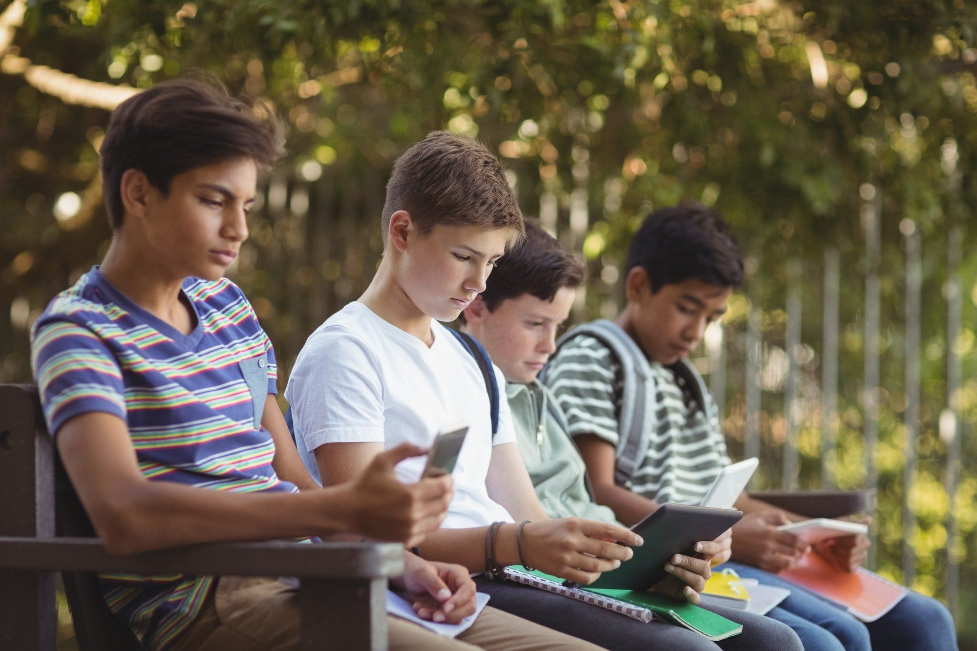 School kids using mobile phone and digital tablet on bench