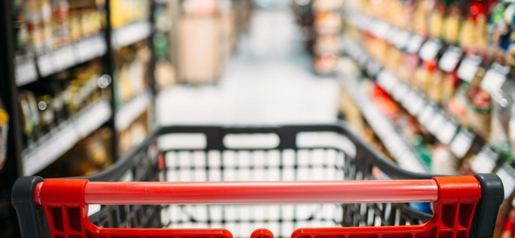 Shopping cart between shelves in food store