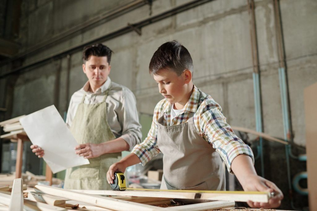 Teenage son working with father in carpentry shop
